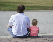 a father sitting with his daughter on a curb