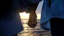 a couple holding hands at a beach