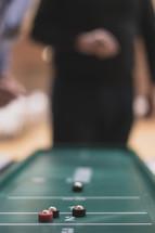 a man playing shuffleboard