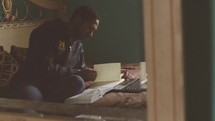 a college student reading a Bible on his bed