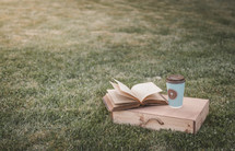 coffee cup with cross on grass with Bible and wood box
