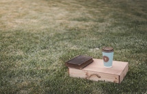 coffee cup with cross, wood box, and Bible on grass