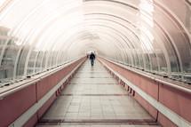 a man walking through a tunnel