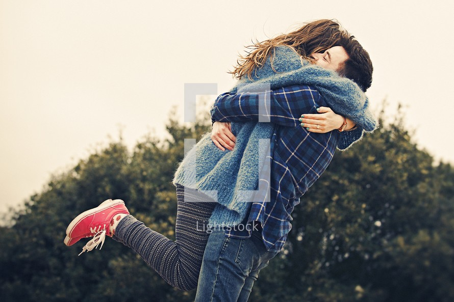a happy young couple hugging outdoors