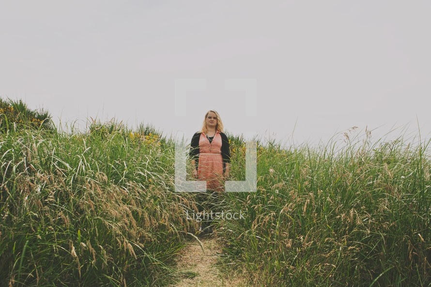woman standing in tall brush