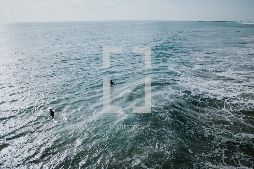 men wading in the ocean