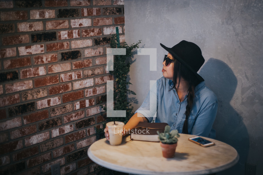 a woman sitting at a table with a Bible