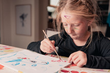 a child painting with watercolor