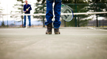 people standing on a tennis court in jeans