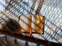 a woman reading a Bible in a hammock