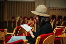a woman sitting in an empty church reading a Bible