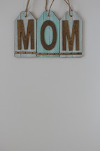 "A blue sign with the word ""mom."""