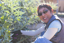 Smiling woman wearing sunglasses while gardening.