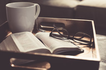 tea cup, open Bible, and reading glasses on a tray