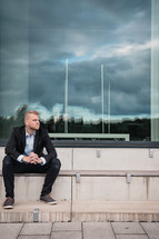 a business man sitting on steps with a reflection of a stormy sky in a window