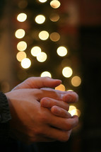 praying hands in front of a Christmas tree