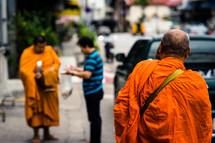 Buddhist monks in orange robes walking on a sidewalk