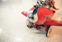 A child sitting in a weathered pedal red airplane .