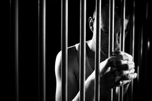 a man holding onto prison bars