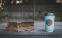 coffee cup with cross and books on wood ledge
