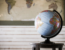 globe on a table and a world map