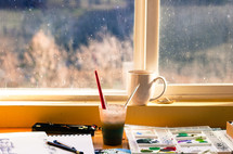 coffee mug and paint supplies in front of a window