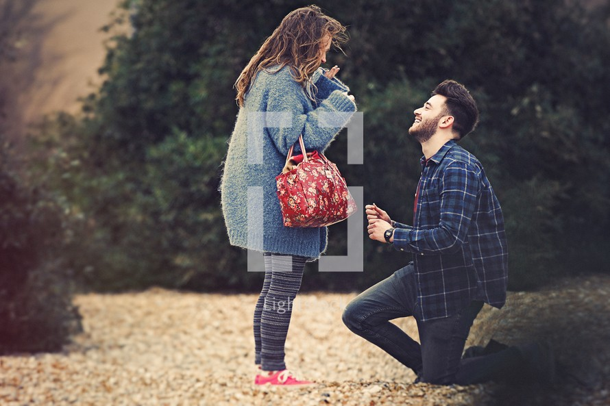 A young man on one knee proposing to a young woman.