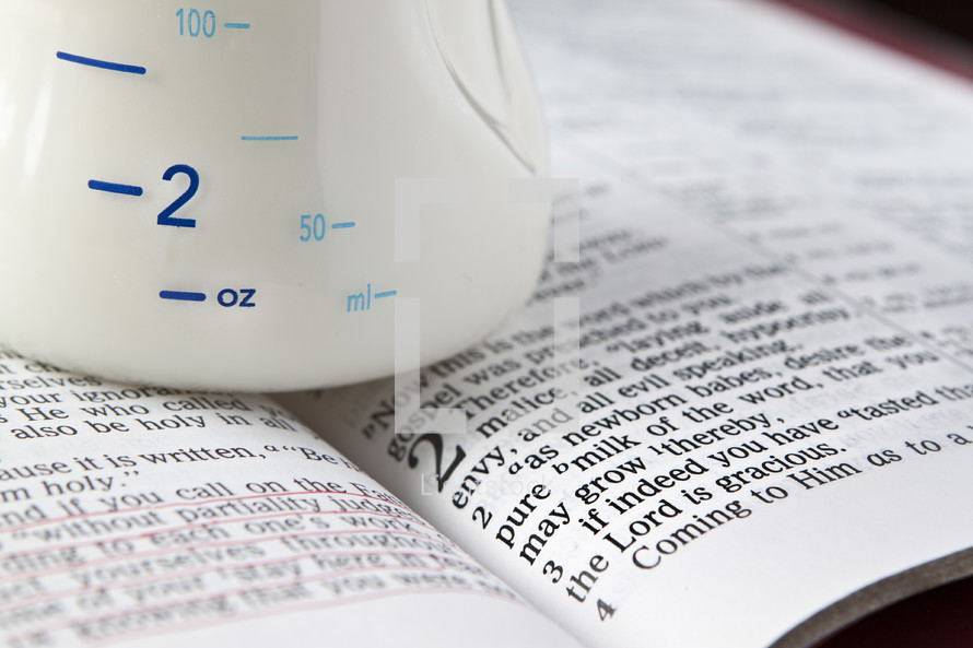 baby bottle resting on the pages of a Bible