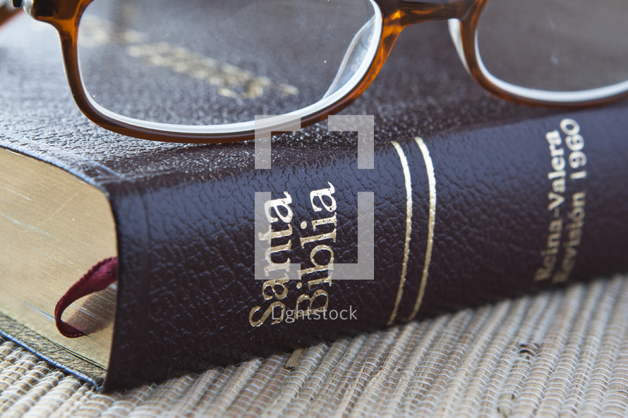 Reading glasses resting on Spanish Bible.