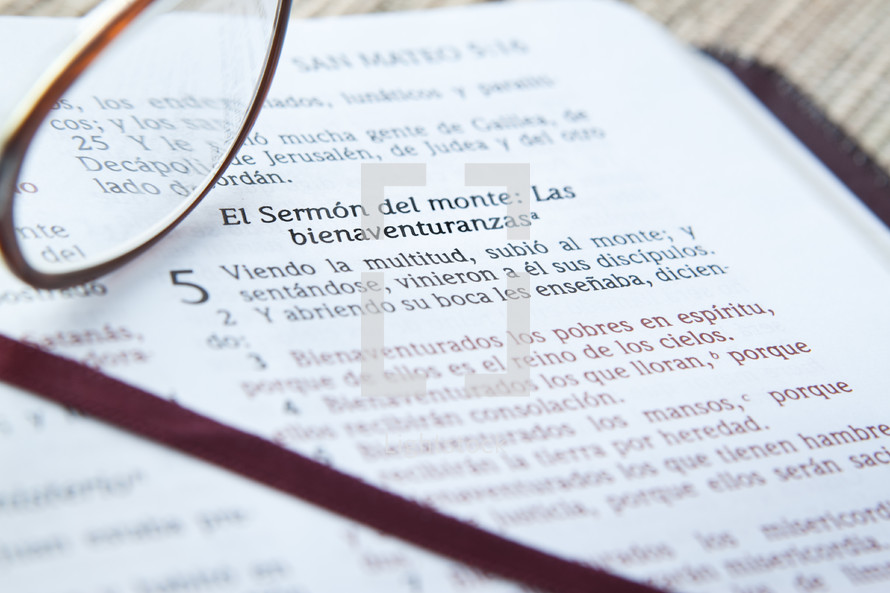 Reading glasses resgin on open page of Spanish Bible.