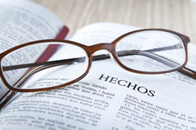 Reading glasses resting on open page of Spanish Bible.