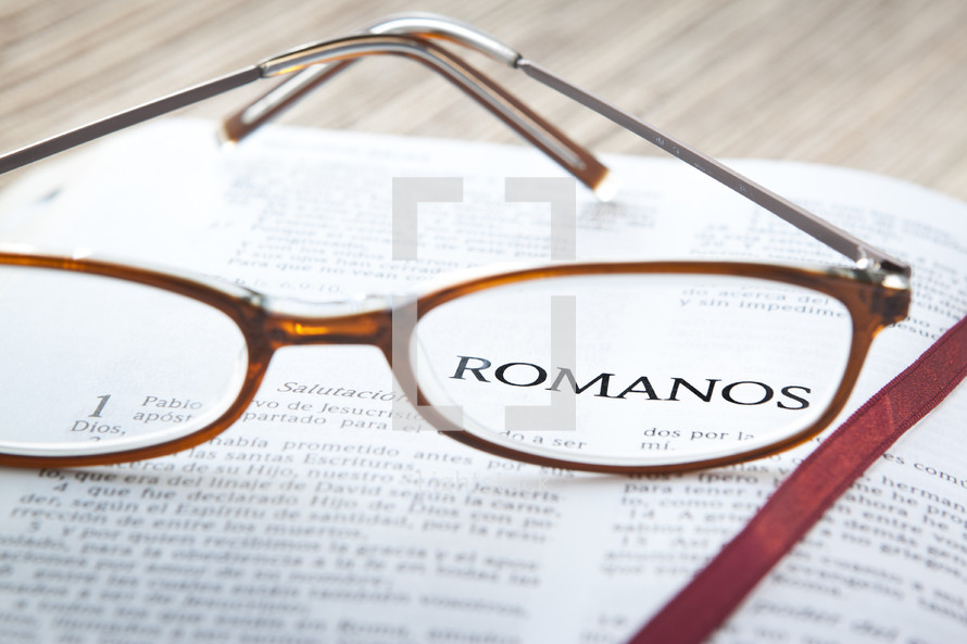 Reading glasses reasting on open page of Spanish Bible.