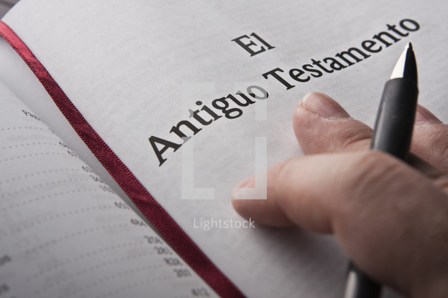 Hand holding pen on Spanish Bible.