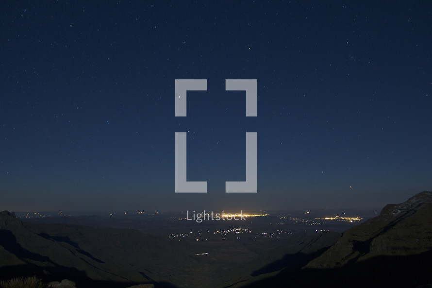 view of lights from a distant city at night standing a the top of a mountain