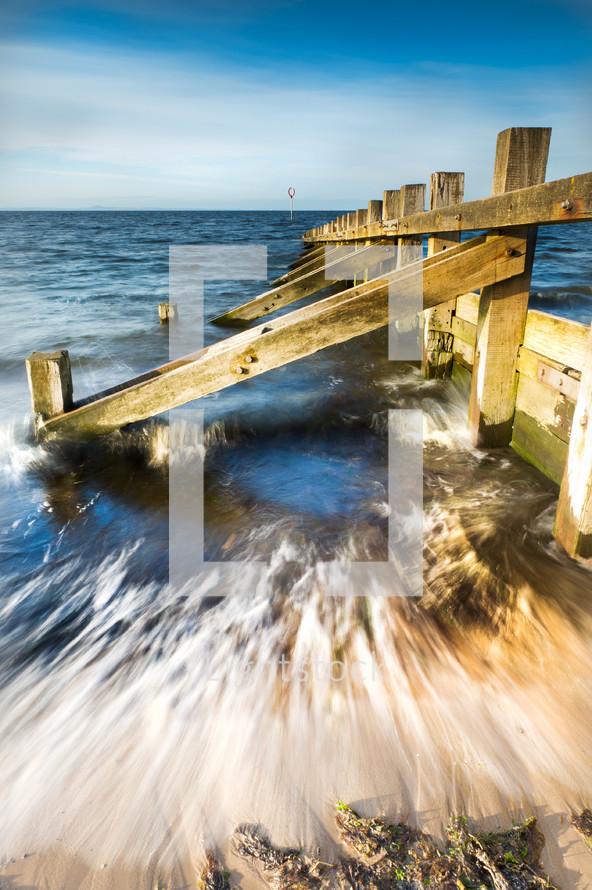 wood dam in ocean - jetty