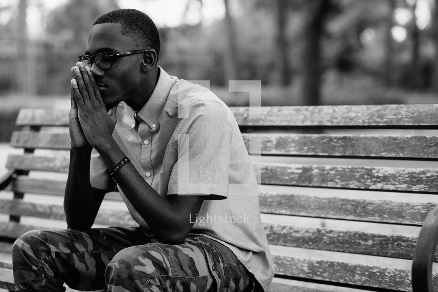 an African-american man sitting on a bench praying outdoors