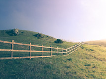Wooden fence in the grass over rolling hills.