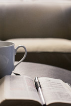 Coffee cup and a pen on the pages of a Bible