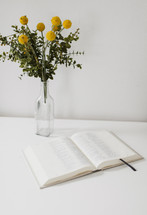 flowers in a vase and an open Bible