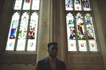 man standing in a church in front of stained glass windows