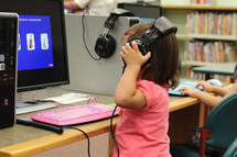 A small girl interacts with a computer at a public library.