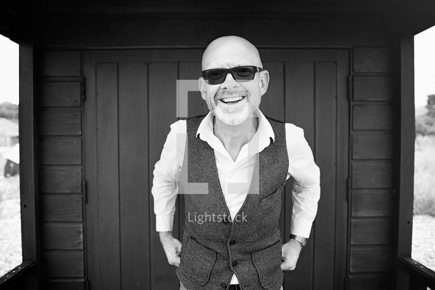 a bald man in sunglasses and a vest