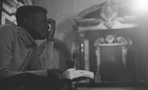 man at a pulpit in prayer holding a Bible