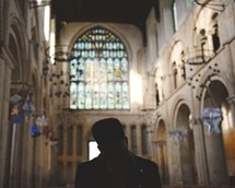 man with head bowed in prayer sitting in an empty church
