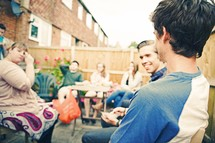 Young people sitting outdoors at a barbecue.