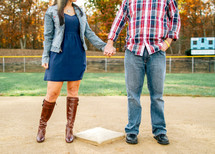 couple holding hands on a baseball field