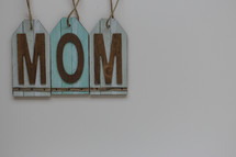"A blue sign reading, ""mom,"" on a white background."