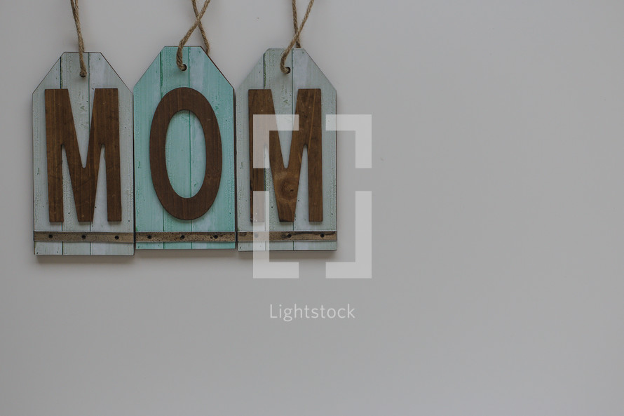 """A blue sign reading, """"mom,"""" on a white background."""