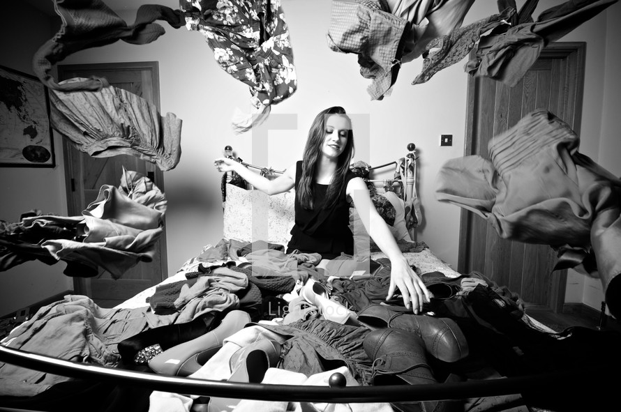 woman sitting on a bed covered in clothes and shoes