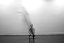 man squatting - white wall - shadow behind